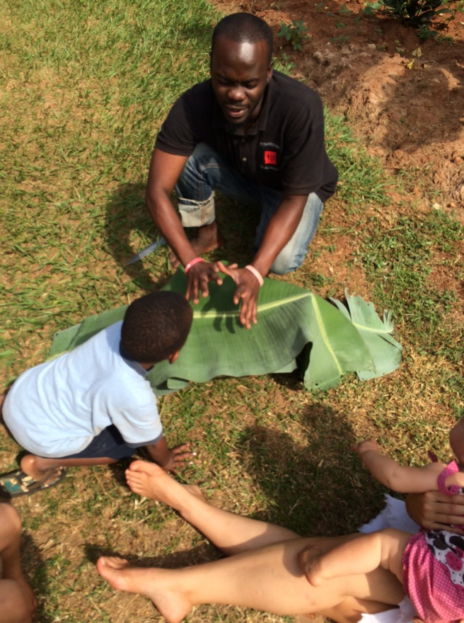 The best cook on the continent teaching us how to steam Posho in banana leaves.